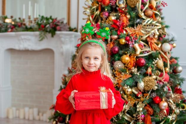 Ein kleines mädchen in der nähe des weihnachtsbaums hält ein geschenk zu hause