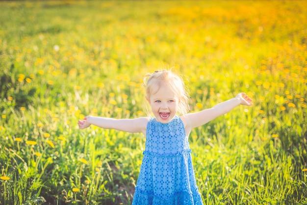 Ein kleines mädchen in einem blauen kleid schreit glücklich