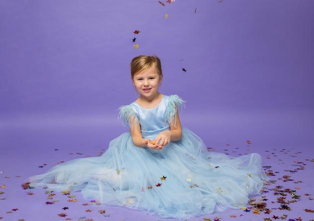 Ein kleines mädchen in einem blauen prinzessinnenkleid in voller länge sitzt mit konfetti auf lila auf dem boden