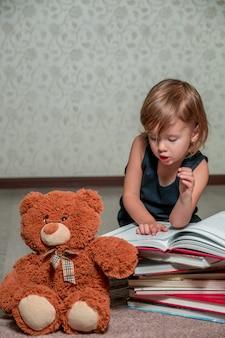 Ein kleines mädchen in einem dunkelblauen kleid ein buch lesend, das auf dem boden nahe teddybären sitzt. kind liest geschichte für spielzeug.
