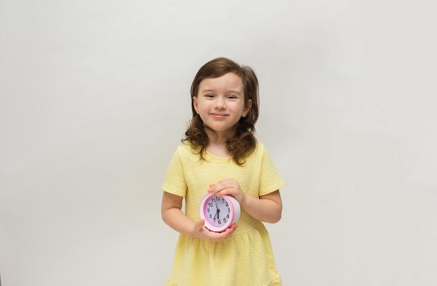 Ein kleines mädchen in einem gelben kleid hält einen tischuhrwecker auf einem weißen hintergrund mit einem platz für text