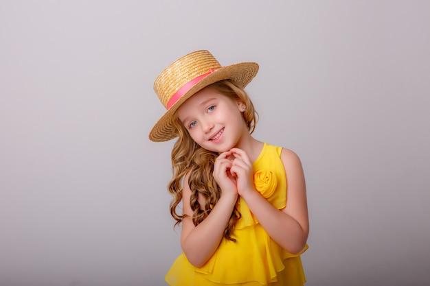 Ein kleines mädchen in einem gelben kleid und einem strohhut