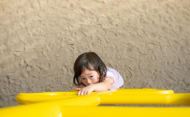 Ein kleines mädchen in einem gestreiften kleid steigt auf einem sandigen spielplatz die treppe hinauf. schießen von oben