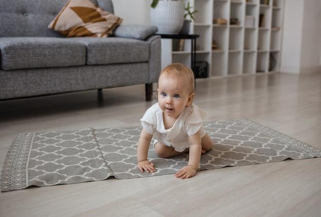 Ein kleines mädchen in einem karmesinroten overall krabbelt auf einem teppich im zimmer