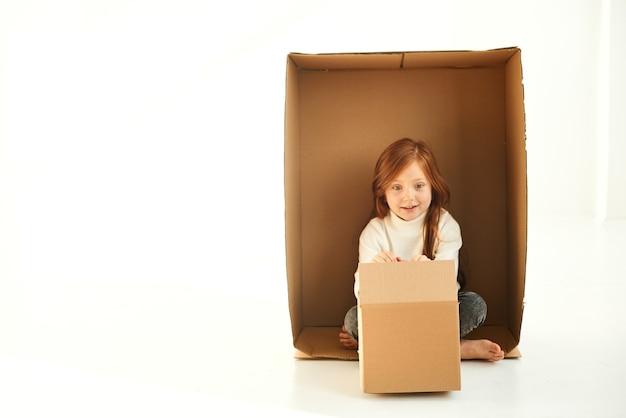 Ein kleines mädchen in einem karton am neuen zuhause