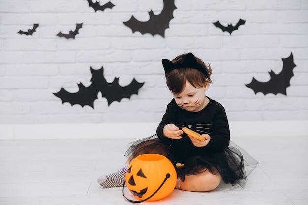 Ein kleines mädchen in einem kostüm der schwarzen katze mit dem kürbiskorb, der einen lebkuchen hält