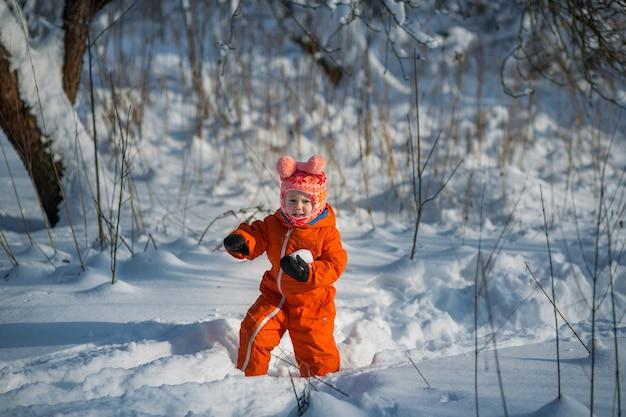 Ein kleines mädchen in einem orangefarbenen overall spielt im winter im wald schneebälle.