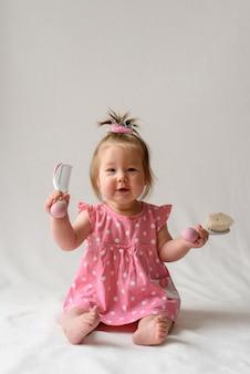 Ein kleines mädchen in einem rosa kleid spielt mit ihrem ersten kamm. mädchen sitzt auf einer weißen oberfläche