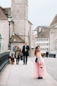 Ein kleines mädchen in einem rosa prinzessinkleid mit einem blumenstrauß in den händen geht durch die altstadt von zürich. porträt eines mädchens in einem rosa kleid auf einer stadtstraße in der schweiz.