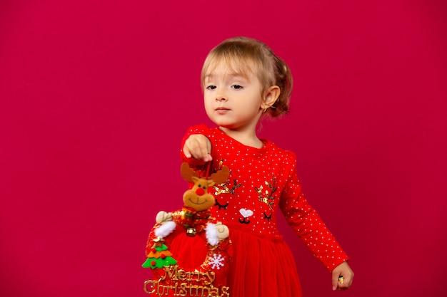 Ein kleines mädchen in einem roten kleid streckt ein efeuhirschspielzeug nach vorne. urlaubskonzept an der roten wand.