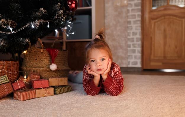 Ein kleines mädchen in einem roten pullover liegt unter dem baum zwischen weihnachtsgeschenken.