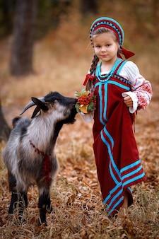 Ein kleines mädchen in einem roten sommerkleid steht neben einer schwarzen jungen ziege im herbstwald
