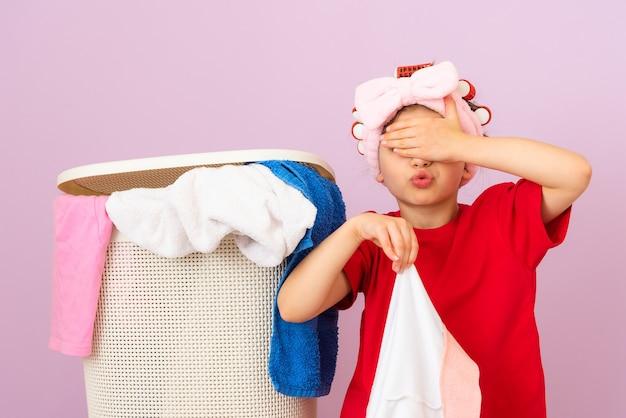 Ein kleines mädchen in einem roten t-shirt und mit lockenwicklern auf dem kopf mag schmutzige kleidung wirklich nicht.