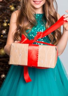 Ein kleines mädchen in einem schicken grünen kleid öffnet ein geschenk. mädchen zieht das rote band. vertikales foto