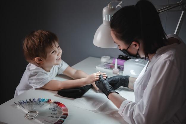 Ein kleines mädchen in einem schönheitssalon. sieht den maniküristen mit schwarzer maske und schwarzen handschuhen an. nagelpflege des kindes.