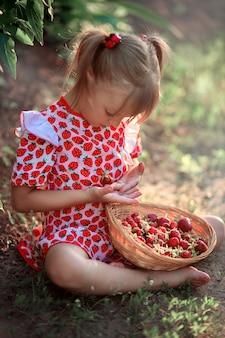 Ein kleines mädchen in einem sommerkleid sitzt auf einer lichtung und hält erdbeeren in den händen