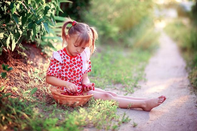 Ein kleines mädchen in einem sommerkleid sitzt auf einer lichtung und pflückt erdbeeren in einem korb