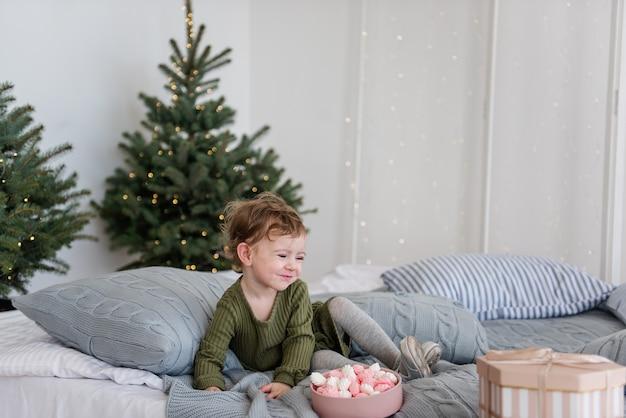 Ein kleines mädchen in einem warmen grünen kleid liegt auf einem weißen bett zwischen grauen strickkissen und isst ein rosa-weißes baiser.