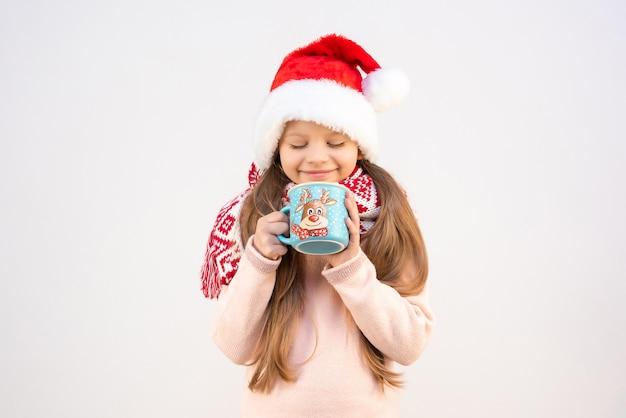 Ein kleines mädchen in einem weihnachtskostüm trinkt ein weihnachtliches heißgetränk aus einer tasse.