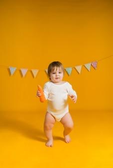 Ein kleines mädchen in einem weißen body geht mit einer karotte auf gelbem grund