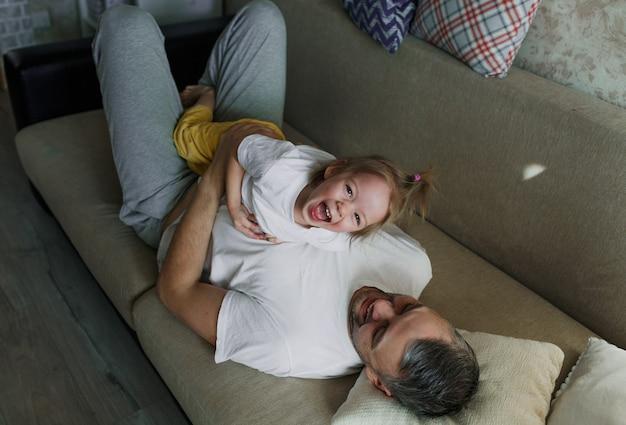 Ein kleines mädchen in einem weißen t-shirt hat spaß daran, mit ihrem vater auf der couch zu spielen und spaß daran zu haben, sich zu amüsieren. sie sehen sich an.