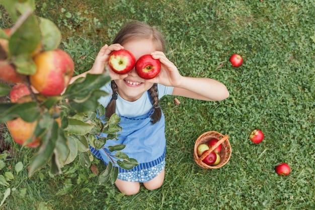 Ein kleines mädchen in einer blauen schürze legte zwei äpfel auf einem grashintergrund in die augen