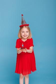 Ein kleines mädchen in einer mütze mit einem kuchen bläst eine kerze aus. alles gute zum geburtstag