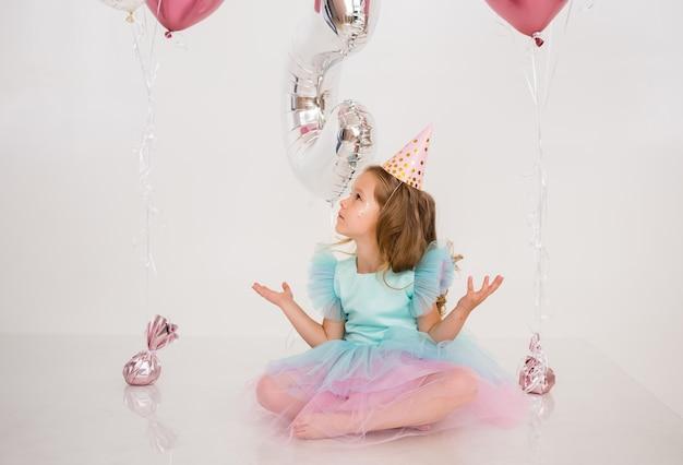 Ein kleines mädchen in einer papiermütze und einem kleid mit tutu-rock sitzt auf dem boden und fängt konfetti auf festlichem hintergrund. festliches bündel luftballons