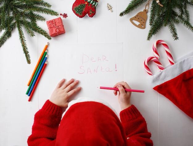Ein kleines mädchen in einer roten weihnachtsmütze schreibt einen brief an den weihnachtsmann.