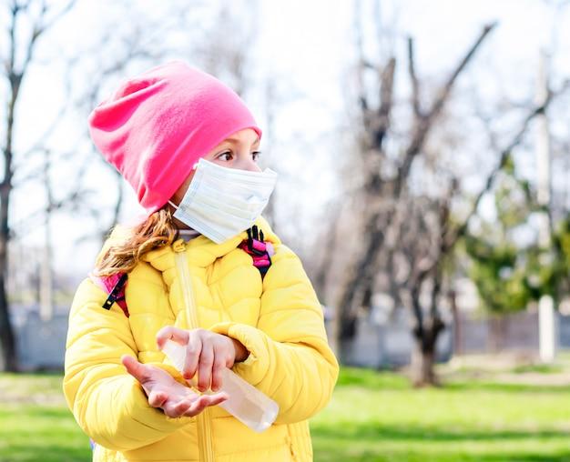 Ein kleines mädchen in einer schutzmaske hält ein händedesinfektionsmittel in den händen.