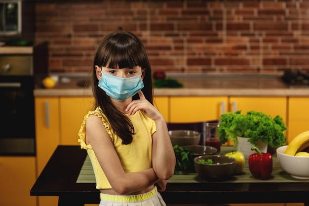 Ein kleines mädchen in einer schutzmaske steht in der küche.