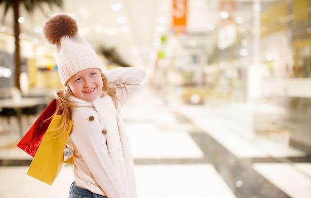 Ein kleines mädchen in einer strickmütze hält mehrfarbige papiertüten in einem einkaufszentrum.