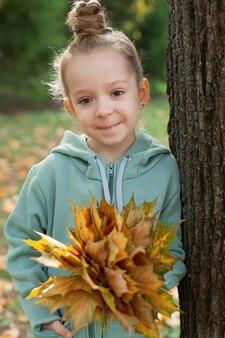 Ein kleines mädchen in einer warmen strickjacke lächelt vor dem hintergrund der abgefallenen blätter und hält einen strauß gelber blätter