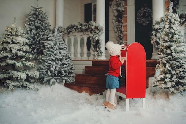Ein kleines mädchen in einer weißen strickmütze wünscht sich etwas, schreibt einen brief an den weihnachtsmann und verschickt eine postkarte per post. wirft einen umschlag in den briefkasten