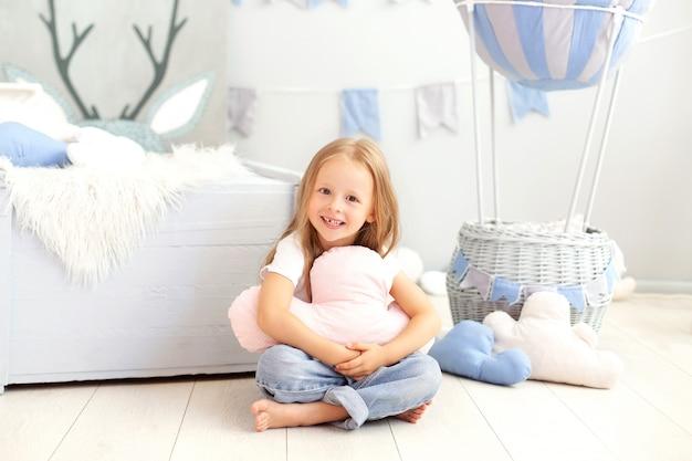 Ein kleines mädchen in freizeitkleidung hält ein wolkenkissen an die wand eines dekorativen ballons. das kind spielt im kinderzimmer. das konzept der kindheit, reisen. geburtstag, feiertagsdekorationen