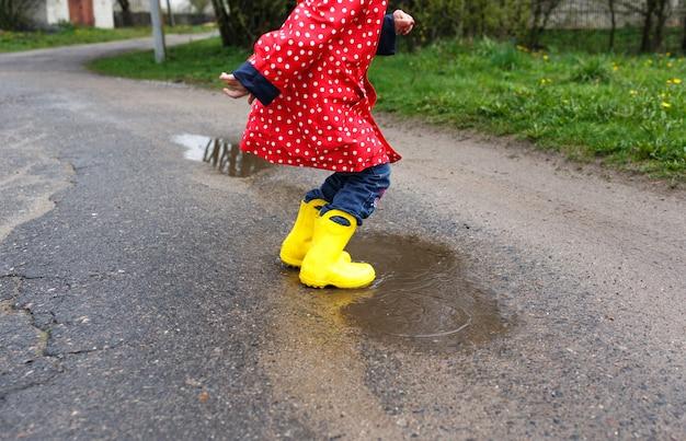 Ein kleines mädchen in gelben stiefeln springt auf frühlingspfützen, nahaufnahme. glückliche kindheit