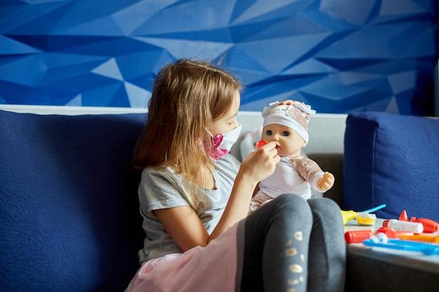 Ein kleines mädchen in medizinischer maske sitzt auf dem sofa, spielt einen arzt, behandelt und hört die puppe mit einem stethoskop in einer medizinischen maske, zu hause während quarantäne und pandemie
