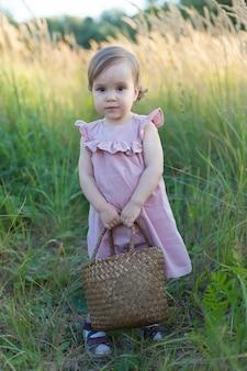 Ein kleines mädchen in pink auf einem feld mit einem korb in den händen. sommerernte von äpfeln und pflaumen.