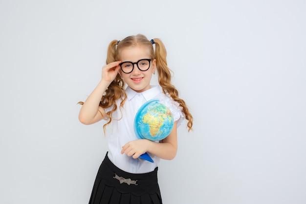Ein kleines mädchen in schuluniform und brille hält einen globus in ihren händen auf einem weißen hintergrund