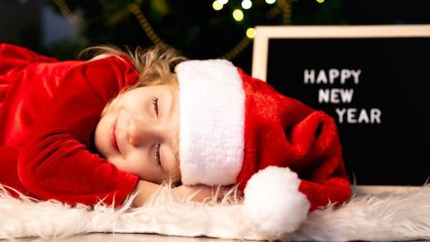 Ein kleines mädchen in weihnachtskostüm und weihnachtsmannmütze schläft unter dem baum und wartet auf ein wunder.