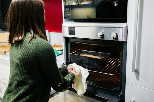 Ein kleines mädchen kocht einen biskuitkuchen im ofen in ihrer wohnküche