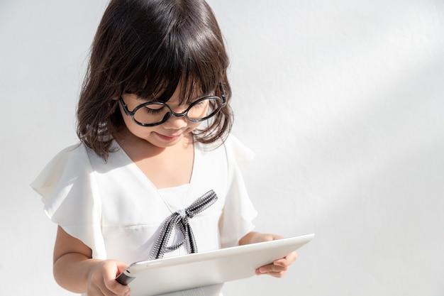 Ein kleines mädchen konzentriert sich auf den tablet-blick auf das tablet-technologiekonzept für kinder