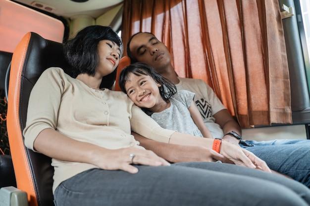 Ein kleines mädchen lächelte auf dem schoß ihrer eltern, die während der fahrt auf dem bussitz schliefen