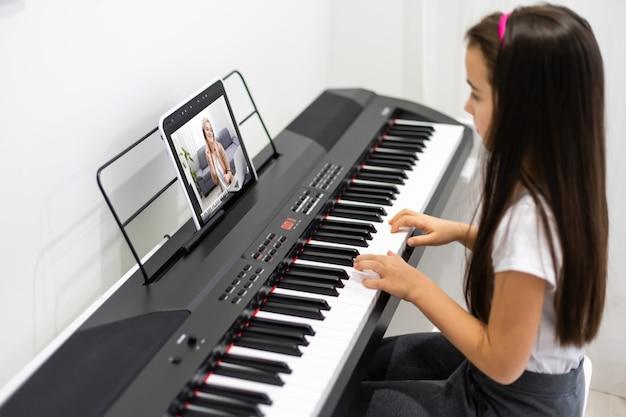 Ein kleines mädchen lernt im videounterricht das klavierspielen. online-fernunterricht während covid-19