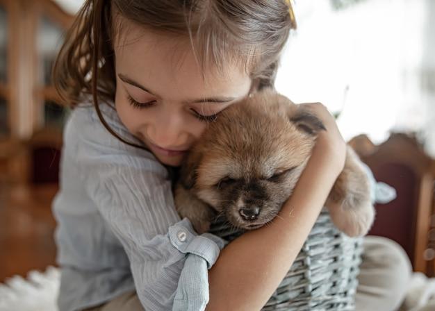 Ein kleines mädchen liebt und umarmt ihren kleinen welpen