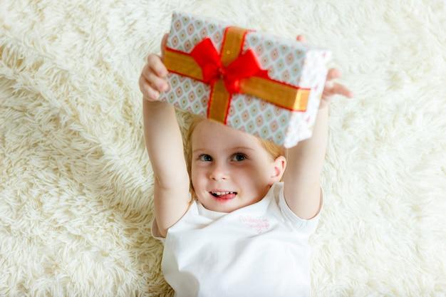 Ein kleines mädchen liegt auf einer decke und hält ein geschenk.