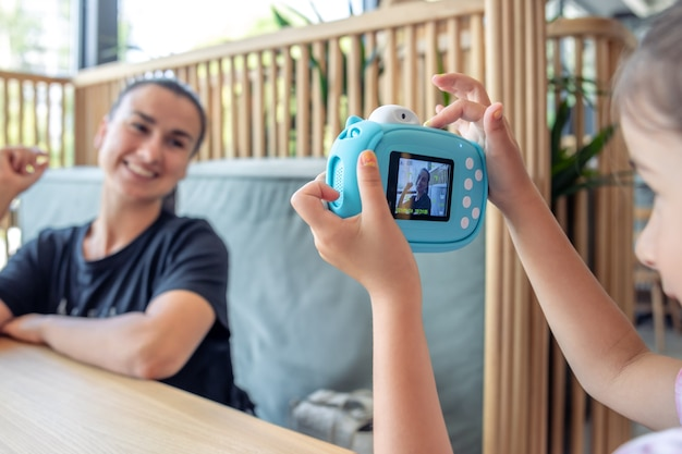 Ein kleines mädchen macht ein foto ihrer mutter mit einer kamera für den sofortigen fotodruck.