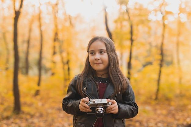 Ein kleines mädchen macht ein foto mit alter retro-kamera im herbstnatur-freizeit- und hobby-konzept