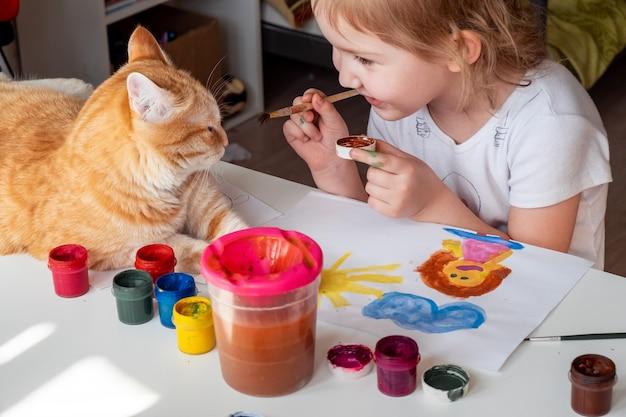 Ein kleines mädchen malt die sonne und ihre mutter mit aquarellen