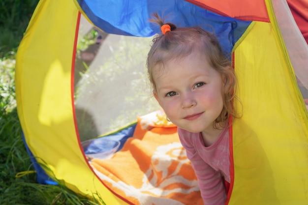 Ein kleines mädchen mit blonden locken schaut aus dem bunten zelt und lächelt.